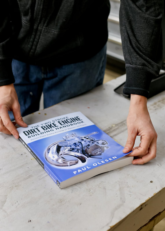 Author, Paul Olesen shows us how thick The Two Stroke Dirt Bike Engine Handbook is